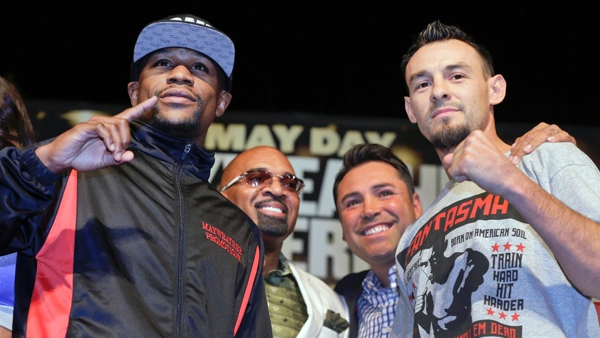 CORRECTS SPELLING TO ELLERBE, INSTEAD OF ELLERBY - Boxers Floyd Mayweather Jr., left, and Robert Guerrero, right, pose for photographers with Mayweather's adviser, Leonard Ellerbe, second from left, and Oscar De La Hoya, during a news conference, Wednesday, May 1, 2013, in Las Vegas. Guerrero will take on Mayweather for Mayweather's WBC welterweight title on Saturday. (AP Photo/Julie Jacobson)