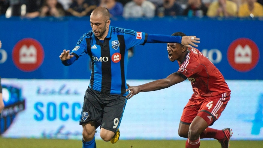 Montreal Impact's Marco Di Vaio, left, breaks away from Toronto FC's Doneil Henry during the fsecond half in the second leg of a semifinal in the Canadian Championship soccer tournament in Montreal, Wednesday, May 1, 2013. (AP Photo/The Canadian Press, Graham Hughes)