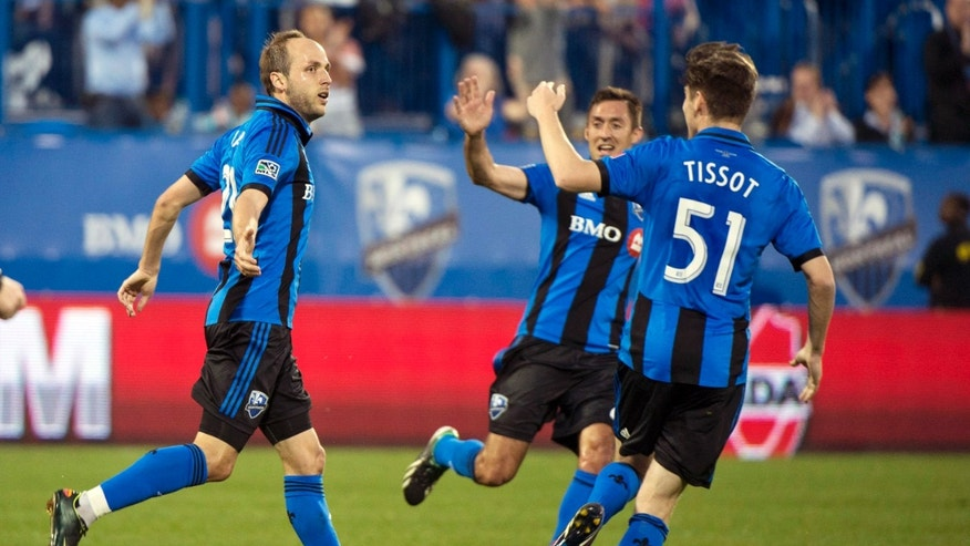 Montreal Impact's Justin Mapp, left, celebrates with Davy Arnaud, center, and Maxim Tissot after scoring against Toronto FC during the first half of their second-leg semifinal Amway Canadian Championship soccer match, Wednesday, May 1, 2013, in Montreal. (AP Photo/The Canadian Press, Graham Hughes)