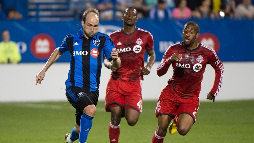 Montreal Impact's Justin Mapp, left, breaks away from Toronto FC's Doneil Henry, center, and Jeremy Hall during the second half of their second-leg semifinal Amway Canadian Championship soccer match, Wednesday, May 1, 2013, in Montreal. (AP Photo/The Canadian Press, Graham Hughes)