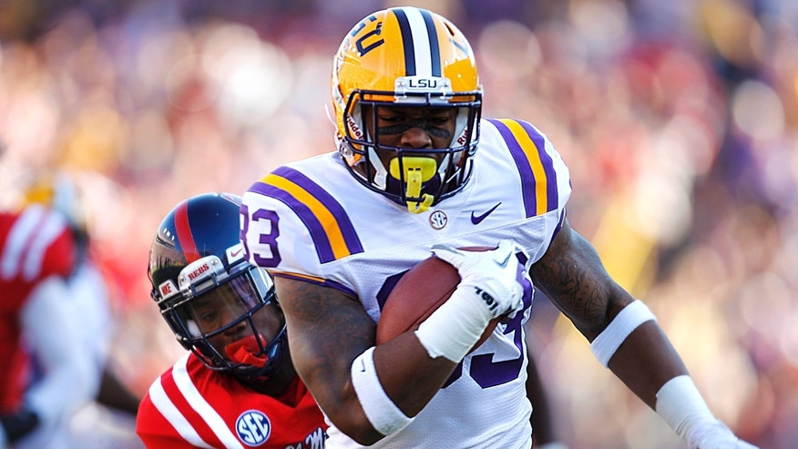 FILE - In this Nov. 17, 2012, file photo, LSU running back Jeremy Hill (33) rushes past Mississippi defensive back Trae Elston (7) on a 27-yard touchdown carry during the first half of their NCAA college football game in Baton Rouge,  Hill, already serving two years' probation in connection with a 2011 arrest, was arrested again early Saturday morning, April 27, 2013, after allegedly punching another man in the side of the head outside a Baton Rouge bar near campus. (AP Photo/Gerald Herbert)