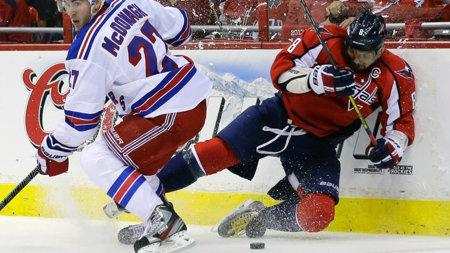 New York Rangers defenseman Ryan McDonagh (27) comes around for the puck after colliding with Washington Capitals left wing Alex Ovechkin (8), from Russia, in the first period of Game 1 of a Stanley Cup NHL playoff hockey series on Thursday, May 2, 2013, in Washington. (AP Photo/Alex Brandon)