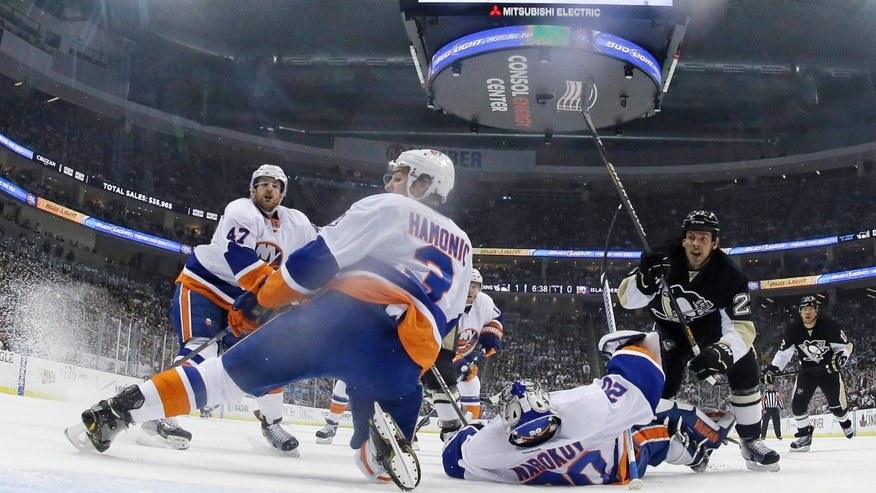 A goal by Pittsburgh Penguins' Pascal Dupuis, not seen, gets past New York Islanders goalie Evgeni Nabokov (20) and defenseman Travis Hamonic (3) during the first period of Game 1 of an NHL hockey Stanley Cup first-round playoff series against the New York Islanders, Wednesday, May 1, 2013, in Pittsburgh. The Penguins won 5-0. (AP Photo/Gene J. Puskar)