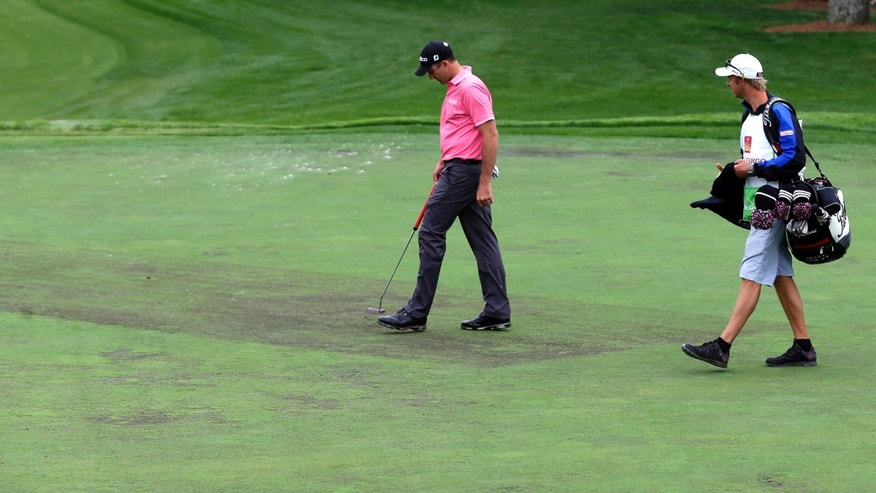 Geoff Ogilvy, center, of Australia, examines the green on the ninth hole during the pro-am of the Wells Fargo Championship golf tournament at Quail Hollow Club in Charlotte, N.C., Wednesday, May 1, 2013. (AP Photo/Chuck Burton)