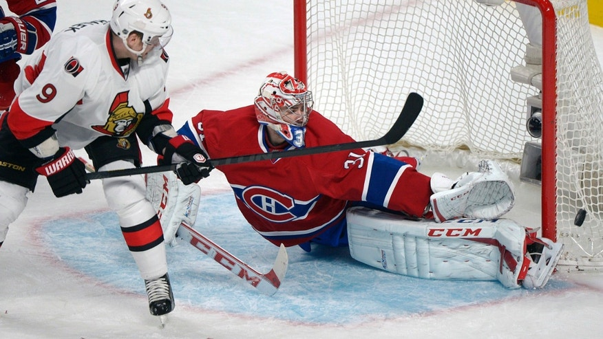 Montreal Canadiens goaltender Carey Price, right, makes a save against Ottawa Senators' Sergei Gonchar (not shown) as Senators forward Milan Michalek (9) looks for the rebound during second-period NHL hockey Game 2 first-round playoff action in Montreal, Friday, May 3, 2013. (AP Photo/The Canadian Press, Graham Hughes)
