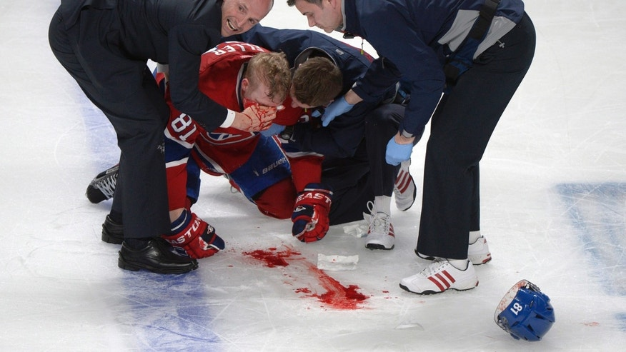 Montreal Canadiens' Lars Eller receives medical attention following a hit by Ottawa Senators' Eric Gryba during the second period of Game 1 of an NHL hockey Stanley Cup playoffs first-round series in Montreal on Thursday, May 2, 2013. (AP Photo/The Canadian Press, Graham Hughes)