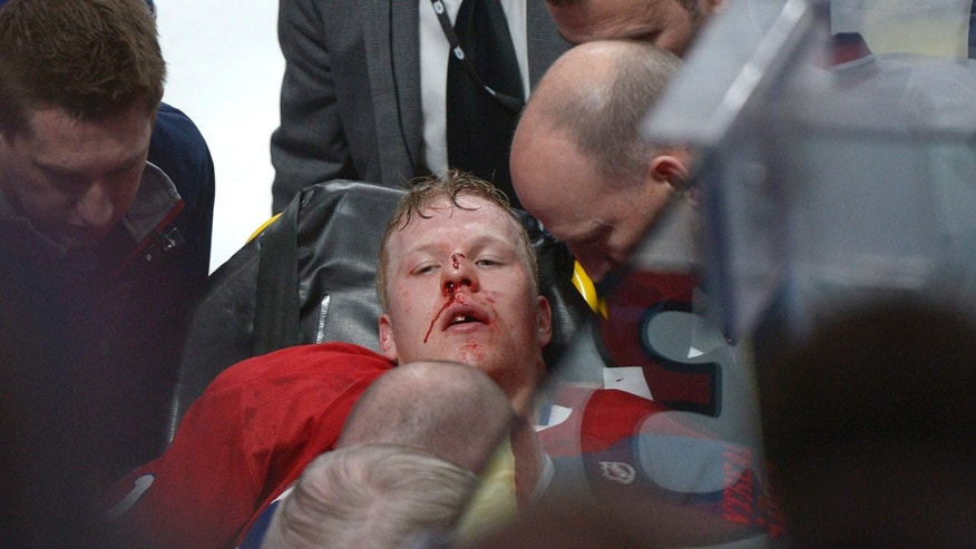 Montreal Canadiens' Lars Eller is taken off the ice following a hit by Ottawa Senators' Eric Gryba during the second period of Game 1 of an NHL hockey Stanley Cup playoffs first-round series in Montreal on Thursday, May 2, 2013. (AP Photo/The Canadian Press, Graham Hughes)