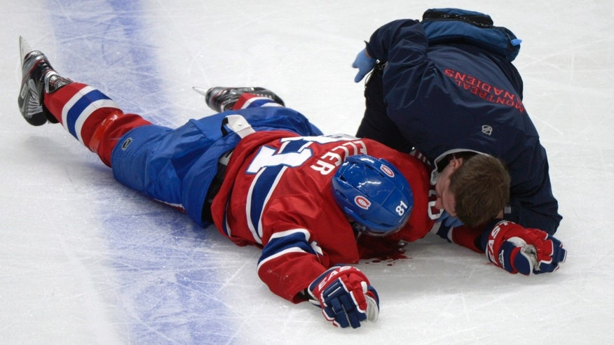 Montreal Canadiens' Lars Eller lies injured on the ice following a hit by Ottawa Senators' Eric Gryba during the second period of Game 1 of an NHL hockey Stanley Cup playoffs first-round series in Montreal on Thursday, May 2, 2013. (AP Photo/The Canadian Press, Graham Hughes)