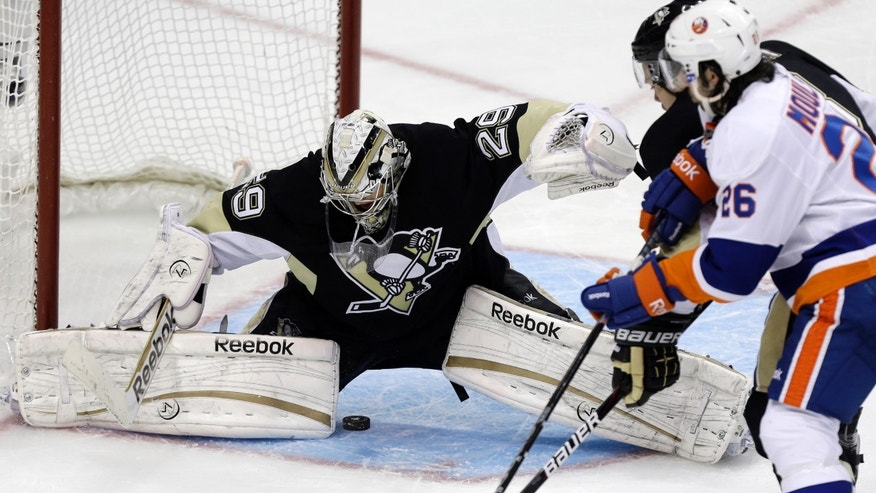 A shot by New York Islanders' Kyle Okposo, not seen, slides between the legs of Pittsburgh Penguins goalie Marc-Andre Fleury (29) during the third period of Game 2 of an NHL hockey Stanley Cup first-round playoff series, Friday, May 3, 2013, in Pittsburgh. The Islanders won 4-3 to even the series at 1-1.(AP Photo/Gene J. Puskar)