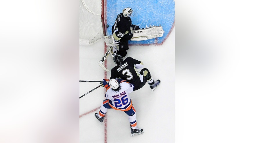 A shot by New York Islanders' Kyle Okposo, not shown, slides behind Pittsburgh Penguins goalie Marc-Andre Fleury (29) during the third period of Game 2 of an NHL hockey Stanley Cup first-round playoff series, Friday, May 3, 2013, in Pittsburgh. At bottom are Islanders' Matt Moulson (26) and Penguins' Douglas Murray. The Islanders won 4-3 to even the series at 1-1. (AP Photo/Gene J. Puskar)