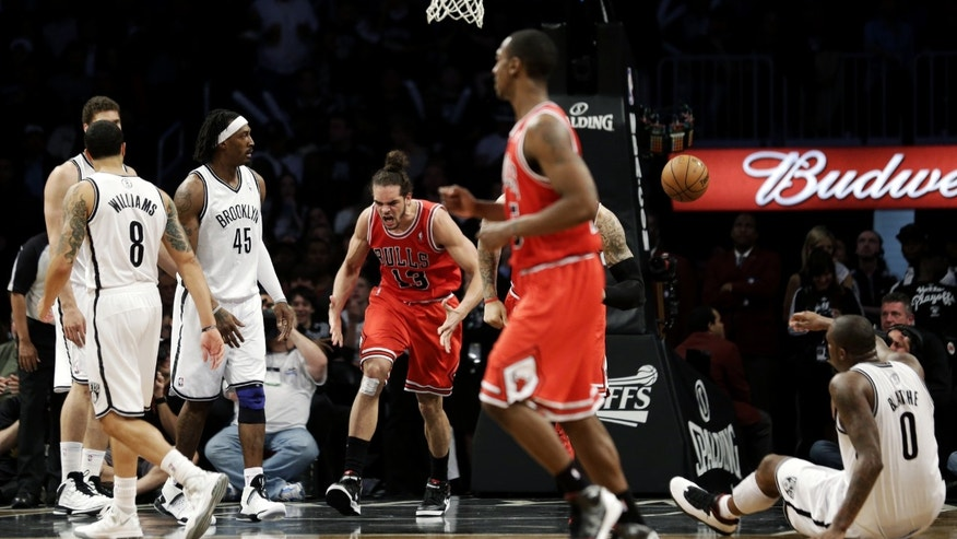 Chicago Bulls center Joakim Noah, center, reacts after scoring in front of Brooklyn Nets' Deron Williams (8) and Gerald Wallace (45) during the first half in Game 7 of their first-round NBA basketball playoff series in New York, Saturday, May 4, 2013. (AP Photo/Julio Cortez)