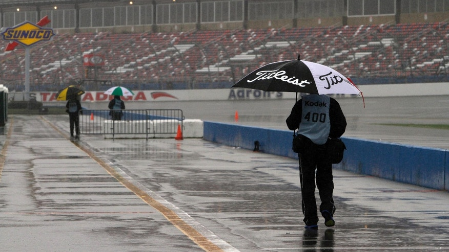 Pit road is virtually empty except for wandering photographers looking for rain features at Talladega Superspeedway in Talladega, Ala., Saturday, May 4, 2013. Rain threatens Saturday's qualifying for Sunday's NASCAR Sprint Cup seires Aaron's 499 auto race. (AP Photo/Butch Dill)