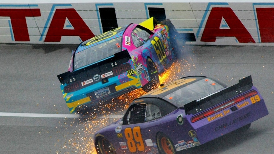 Travis Pastrana (60) crashes in Turn 3 along with Morgan Shepherd (89) during the NASCAR Nationwide Series auto race at the Talladega Superspeedway in Talladega, Ala., Saturday, May 4, 2013. (AP Photo/Greg McWilliams)