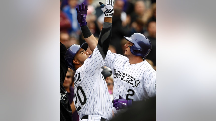 Colorado Rockies' Wilin Rosario, left, congratulates teammate Troy Tulowitzki who returns to the dugout after hitting a solo home run against the Tampa Bay Rays in the fourth inning of a baseball game in Denver, Sunday, May 5, 2013. (AP Photo/David Zalubowski)