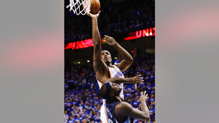 Oklahoma City Thunder forward Serge Ibaka (9) shoots against Memphis Grizzlies power forward Zach Randolph (50) during the quarter of Game 1 of their Western Conference Semifinals NBA basketball playoff series in Oklahoma City, Sunday, May 5, 2013. (AP Photo/Alonzo Adams)