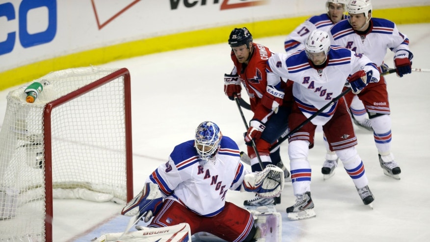 New York Rangers goalie Henrik Lundqvist, left, of Sweden, makes a save during the third period in Game 2 of an NHL hockey Stanley Cup first-round playoff series against the Washington Capitals on Saturday, May 4, 2013, in Washington. The Capitals defeated the Rangers 1-0 in overtime. From left, Lundgvist, Washington Capitals left wing Jason Chimera, New York Rangers defenseman Anton Stralman, New York Rangers defenseman John Moore, and New York Rangers right wing Derek Dorsett. (AP Photo/Evan Vucci)