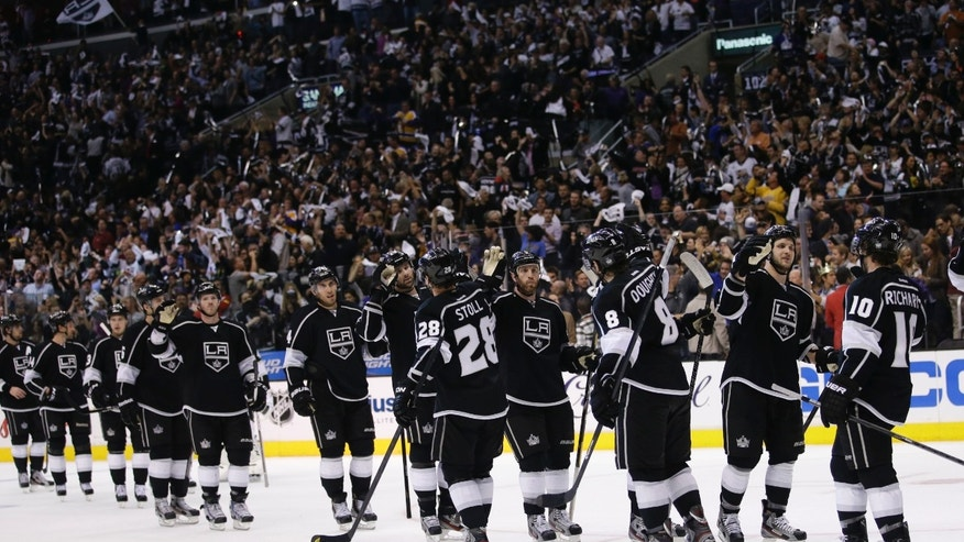 The Los Angeles Kings celebrate their team's 1-0 win against the St. Louis Blues after Game 3 of a first-round NHL hockey Stanley Cup playoff series in Los Angeles, Saturday, May 4, 2013. (AP Photo/Jae C. Hong)