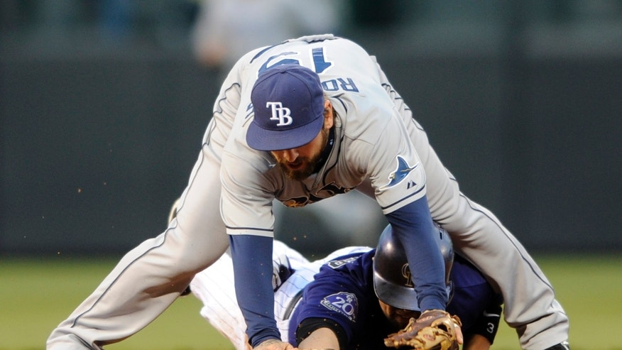 Tampa Bay Rays second baseman Ryan Roberts (19) straddles Colorado Rockies' Michael Cuddyer (3) after forcing him out during the third inning of a baseball game Saturday, May 4, 2013, in Denver. (AP Photo/Jack Dempsey)
