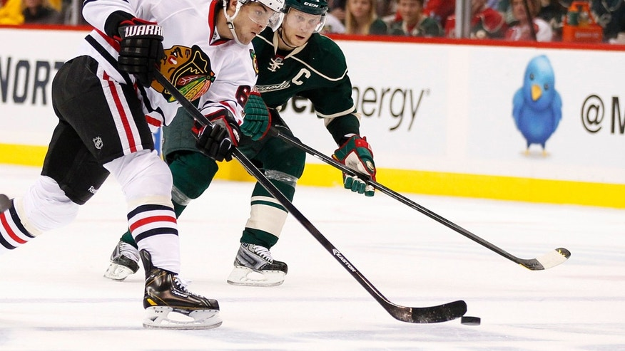 Chicago Blackhawks' Michael Frolik (27) shoots against Minnesota Wild's Mikko Koivu in the second period of Game 3 of an NHL hockey Stanley Cup playoff series Sunday, May 5, 2013 in St. Paul, Minn.(AP Photo/Andy King)