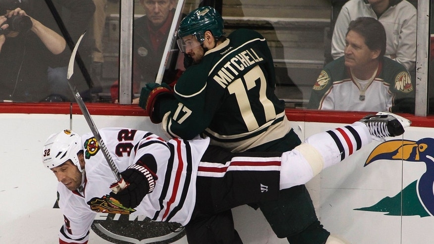 Chicago Blackhawks' Michal Rozsival (32) is taken down by Minnesota Wild's Torrey Mitchell in the third period of Game 3 of an NHL hockey Stanley Cup playoff series Sunday, May 5, 2013 in St. Paul, Minn. Minnesota defeated the Blackhawks 3-2 on overtime.(AP Photo/Andy King)s