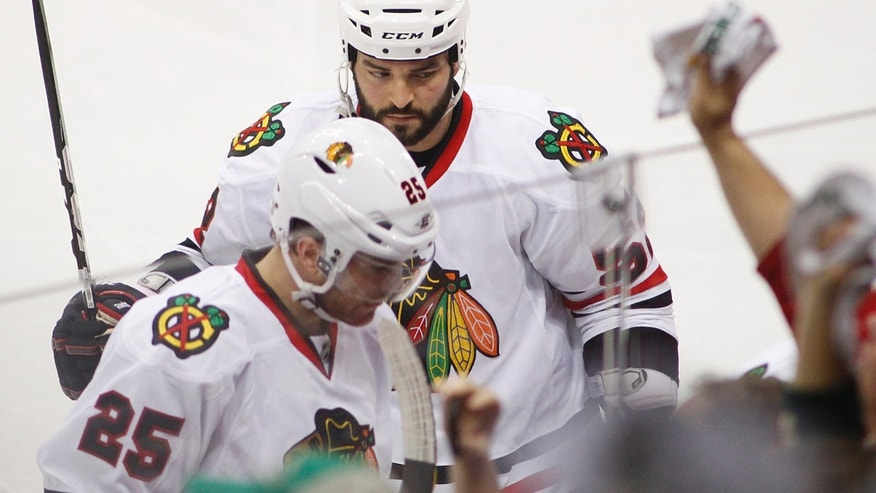 Chicago Blackhawks players Brandon Bollig, top, and Viktor Stalberg leave the ice after Minnesota Wild's Jason Zucker scored a goal in the fourth period during Game 3 of an NHL hockey Stanley Cup playoff series Sunday, May 5, 2013 in St. Paul, Minn. The Wild defeated the Blackhawks 3-2. (AP Photo/Andy King)