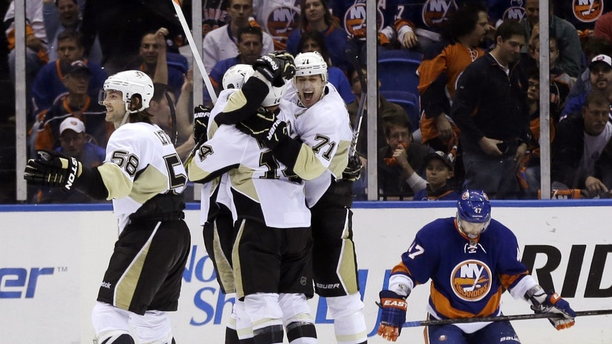 Pittsburgh Penguins' Chris Kunitz (14) celebrates his goal with teammates Kris Letang (58) and Evgeni Malkin (71) while New York Islanders' Andrew MacDonald, right, reacts during overtime of Game 3 of an NHL hockey Stanley Cup first-round playoff series, Sunday, May 5, 2013, in Uniondale, N.Y. The Penguins won 5-4. (AP Photo/Seth Wenig)