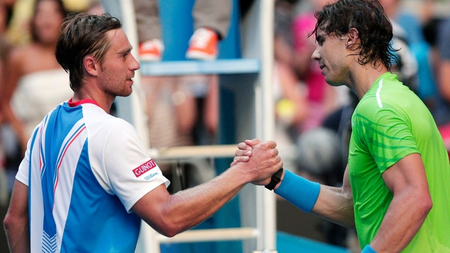 FILE - In this Jan. 16, 2012, file photo, Spain's Rafael Nadal shakes hands with Alex Kuznetsov, left, following their first-round match at the Australian Open tennis championship, in Melbourne, Australia. Kuznetsov has made it to French Open's main draw with a USTA wild card. (AP Photo/Rick Rycroft, File)