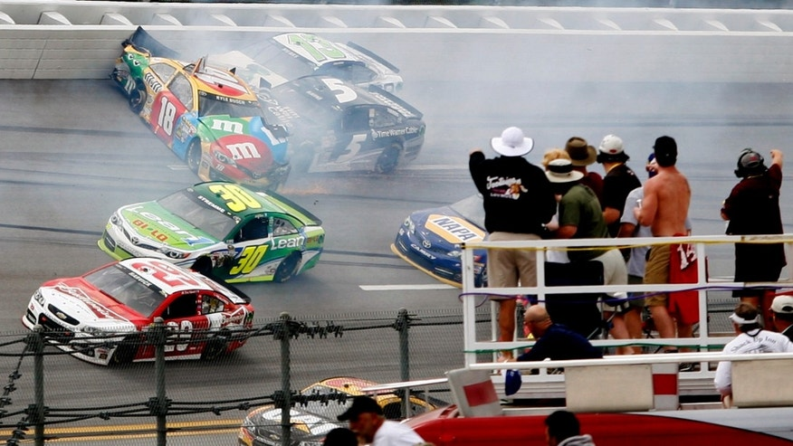 Fans watch as cars crash in Turn 1 during the NASCAR Sprint Cup Series Aaron's 499 auto race at Talladega Superspeedway in Talladega, Ala., Sunday, May 5, 2013. Casey Mears (13) and Kasey Kahne (5) crash into Kyle Busch (18) as Kevin Harvick (29) and David Stremme (30) try to avoid the accident. (AP Photo/Skip Williams)