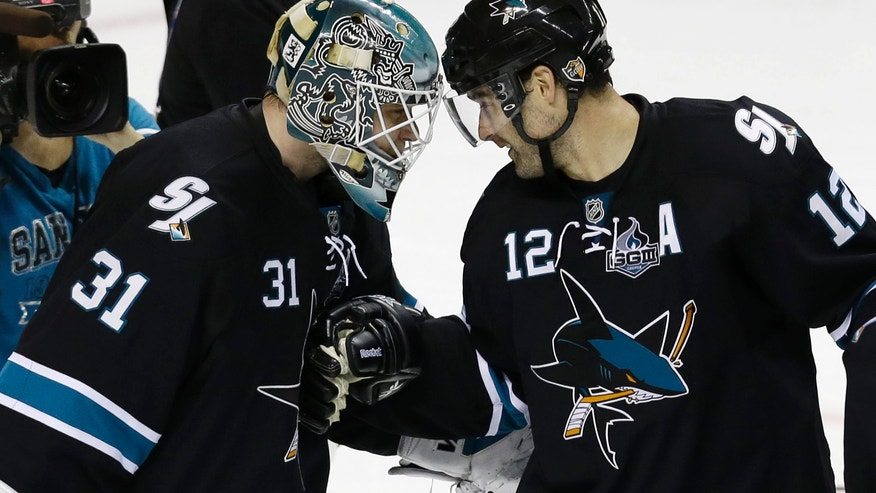 San Jose Sharks' Antti Niemi, of Finland, left, celebrates with teammate Patrick Marleau after a 5-2 win over the Vancouver Canucks during Game 3 of their first-round NHL hockey Stanley Cup playoff series in San Jose, Calif., Sunday, May 5, 2013. (AP Photo/Marcio Jose Sanchez)