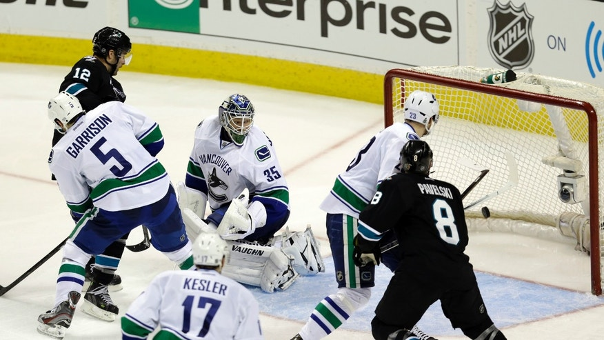 A shot from San Jose Sharks center Logan Couture gets past Vancouver Canucks goalie Cory Schneider (35) for a goal during the third period of Game 3 of their first-round NHL hockey Stanley Cup playoff series in San Jose, Calif., Sunday, May 5, 2013. (AP Photo/Marcio Jose Sanchez)