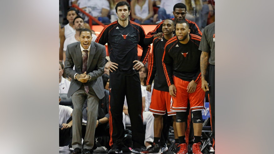 The Chicago Bulls bench, from left, Derrick Rose, Vladimir Radmanovic, Marquis Teague, Nazr Mohammed and Daequan Cook react during the second half in Game 1 of their NBA basketball playoff series in the Eastern Conference semifinals against the Miami Heat, Monday, May 6, 2013, in Miami. The Bulls defeated the Heat 93-86. (AP Photo/Lynne Sladky)