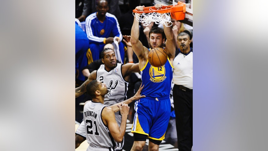 Golden State Warriors center Andrew Bogut (12) dunks against San Antonio Spurs small forward Kawhi Leonard (2) and Tim Duncan (21) during the first half of Game 1 of the Western Conference semifinal NBA basketball playoff series, Monday, May 6, 2013, in San Antonio. (AP Photo/Darren Abate)