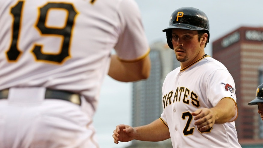 Pittsburgh Pirates' Travis Snider, right, returns to the dugout after scoring on a double by Pirates' Andrew McCutchen during the first inning of an interleague baseball game against the Seattle Mariners in Pittsburgh, Tuesday, May 7, 2013. (AP Photo/Gene J. Puskar)
