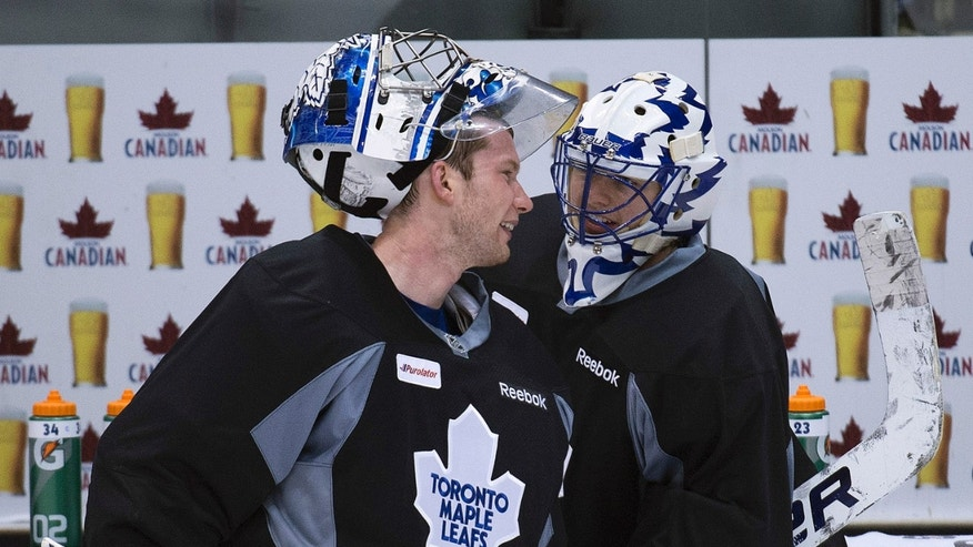 Toronto Maple Leafs goalies James Reimer, left, and Ben Scrivens, right, talk during hockey practice in Toronto on Tuesday, May 7, 2013. The Leafs trail the Boston Bruins 2-1 in their best-of-seven games first-round NHL hockey Stanley Cup playoff series. Game 4 is scheduled for Wednesday in Toronto. (AP Photo/The Canadian Press, Nathan Denette)