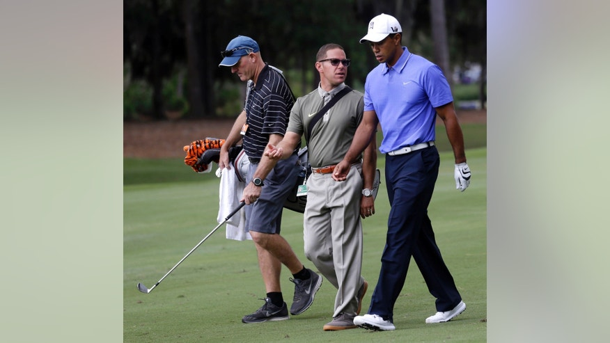 Tiger Woods walks with his caddie Joe LaCava, left, and golfing coach Sean Foley, during practice rounds of the Players Championship golf tournament at TPC Sawgrass in Ponte Vedra Beach, Fla., Tuesday, May 7, 2013. (AP Photo/Gerald Herbert)