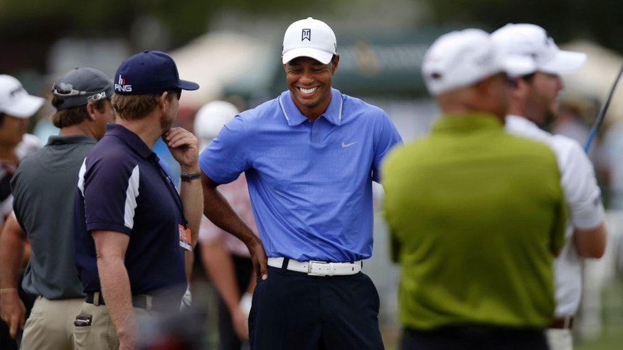 Tiger Woods laughs as he mingles with fellow golfers on the practice range during a practice round at The Players Championship golf tournament at TPC Sawgrass in Ponte Vedra Beach, Fla., Tuesday, May 7, 2013. (AP Photo/Gerald Herbert)