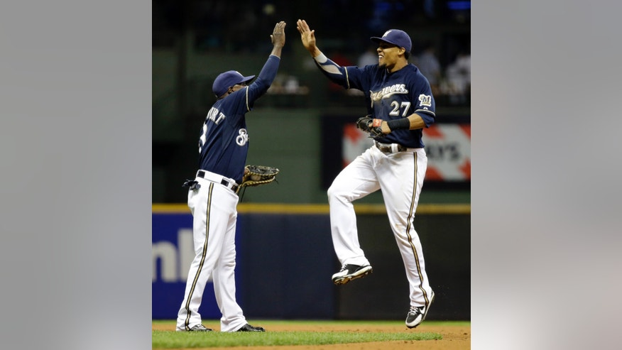Milwaukee Brewers' Yuniesky Betancourt and Carlos Gomez (27) celebrate after a baseball game against the Texas Rangers on Tuesday, May 7, 2013, in Milwaukee. The Brewers won 6-3. (AP Photo/Morry Gash)