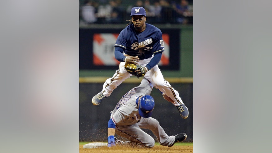 Milwaukee Brewers' Rickie Weeks leaps over Texas Rangers' Craig Gentry while turning a double play on a ball hit by Lance Berkman during the seventh inning of a baseball game Tuesday, May 7, 2013, in Milwaukee. (AP Photo/Morry Gash)
