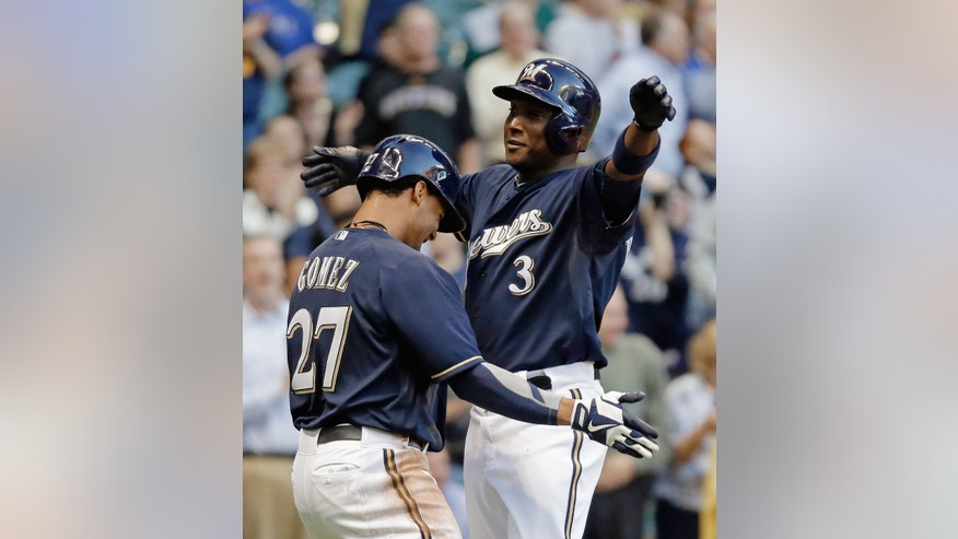 Milwaukee Brewers' Yuniesky Betancourt (3) is congratulated by Carlos Gomez (27) after Betancourt hit a two-run home run during the first inning of a baseball game against the Texas Rangers on Tuesday, May 7, 2013, in Milwaukee. (AP Photo/Morry Gash)