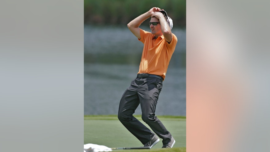 Justin Rose, of England, reacts as playing partner Lee Westwood nearly holes out on the 17th hole during a practice round at The Players Championship golf tournament at TPC Sawgrass in Ponte Vedra Beach, Fla., Wednesday, May 8, 2013. (AP Photo/Chris O'Meara)