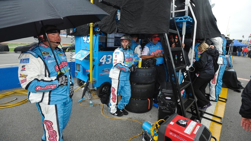 The pit crew of NASCAR Sprint Cup Series driver Aric Almirola waits for the rain to stop during a rain delayed Aaron's 499 auto race at Talladega Superspeedway in Talladega, Ala., Sunday, May 5, 2013. (AP Photo/Rainier Ehrhardt)