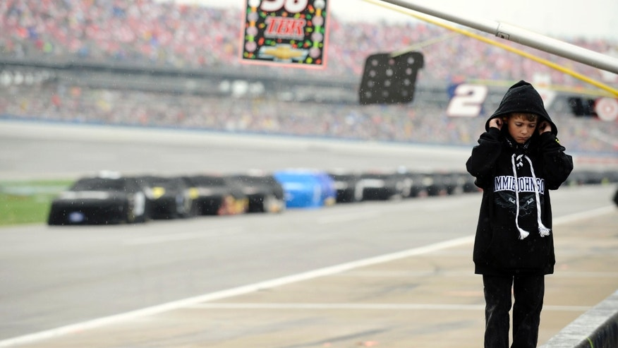 Logan Drumheller, 10, of Fishersville, Va., reacts on pit road after officials red-flagged the NASCAR Sprint Cup Series Aaron's 499 auto race because of rain at Talladega Superspeedway in Talladega, Ala., Sunday, May 5, 2013. (AP Photo/Rainier Ehrhardt)