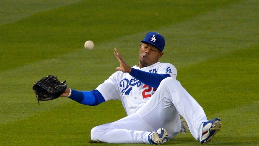 Los Angeles Dodgers left fielder Carl Crawford can't handle a ball hit for an RBI triple by Arizona Diamondbacks' Trevor Cahill during the second inning of their baseball game, Monday, May 6, 2013, in Los Angeles. (AP Photo/Mark J. Terrill)
