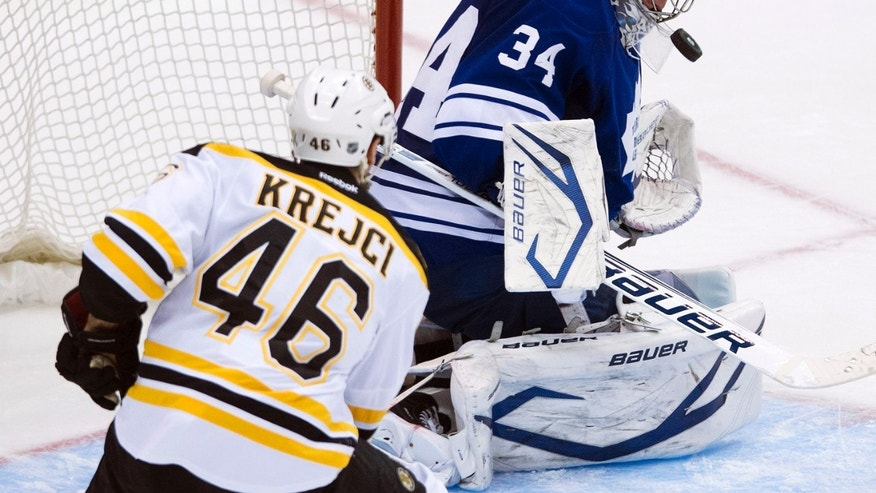 Toronto Maple Leafs goalie James Reimer, right, lets out a rebound against Boston Bruins forward David Krejci, left, during the second period of Game 4 of their NHL hockey Stanley Cup playoff series, Wednesday, May 8, 2013, in Toronto. (AP Photo/The Canadian Press, Nathan Denette)