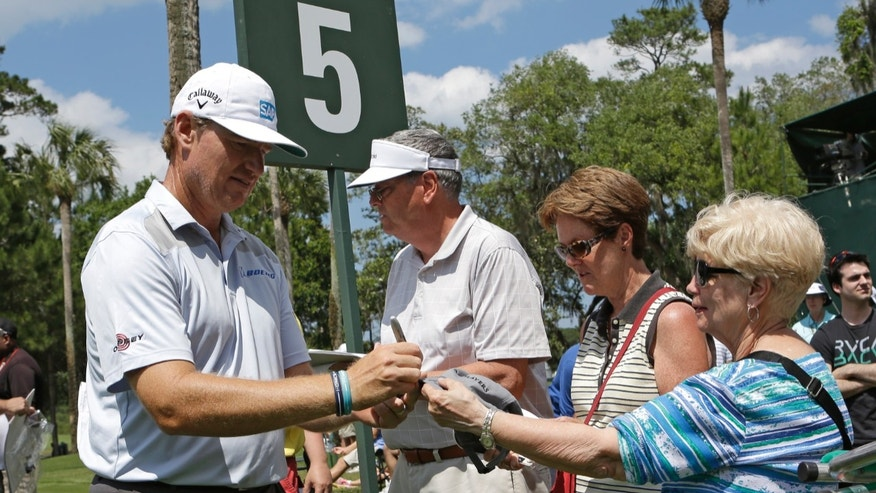 Ernie Els, of South Africa, signs autographs for fans after putting on the fifth green during a practice round at The Players championship golf tournament at TPC Sawgrass in Ponte Vedra Beach, Fla., Wednesday, May 8, 2013.(AP Photo/John Raoux)