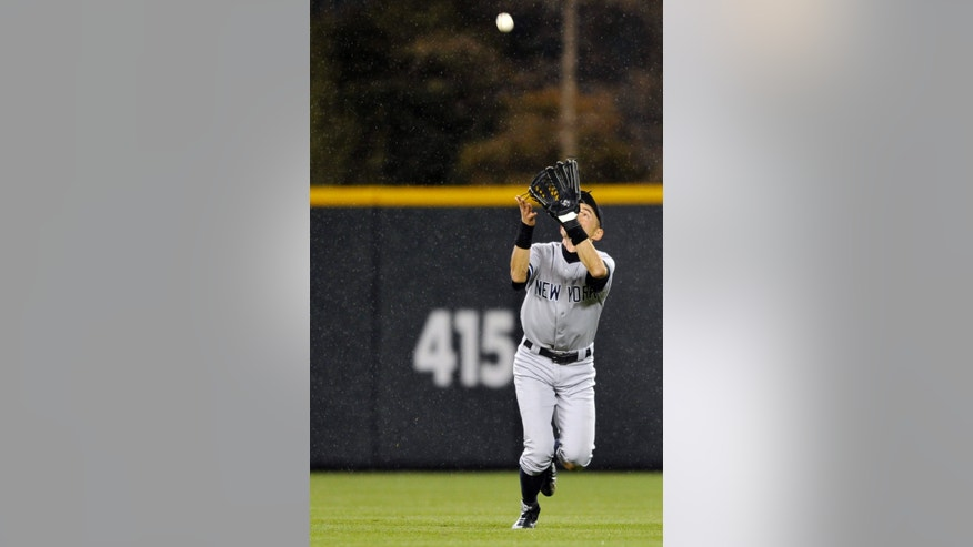 New York Yankees' Ichiro Suzuki, of Japan, catches a fly ball hit by Colorado Rockies' Yorvit Torrealba (8) during the fifth inning of a baseball game, Tuesday, May 7, 2013, in Denver. (AP Photo/Jack Dempsey)