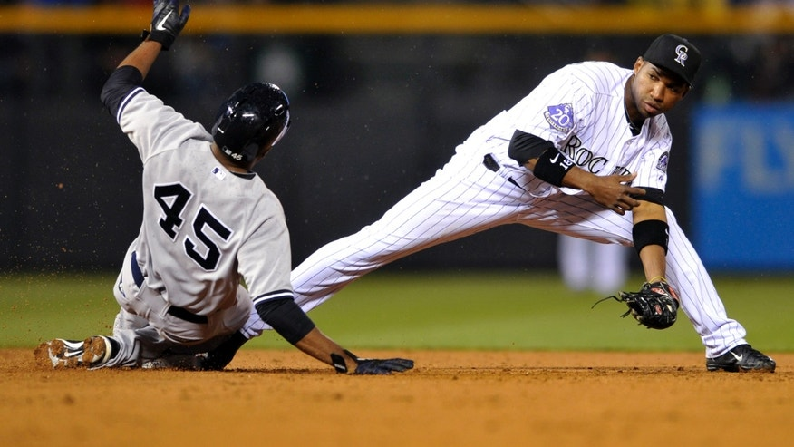 Colorado Rockies second baseman Jonathan Herrera (18) forces out New York Yankees' Ben Francisco (45) at second during the fourth inning of a baseball game, Tuesday, May 7, 2013, in Denver. (AP Photo/Jack Dempsey)