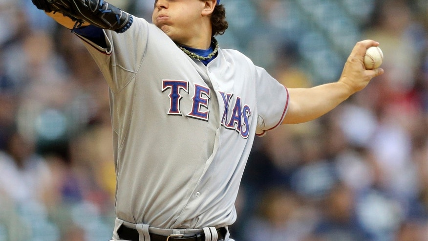 Texas Rangers starting pitcher Derek Holland throws during the first inning of a baseball game against the Milwaukee Brewers Wednesday, May 8, 2013, in Milwaukee. (AP Photo/Morry Gash)