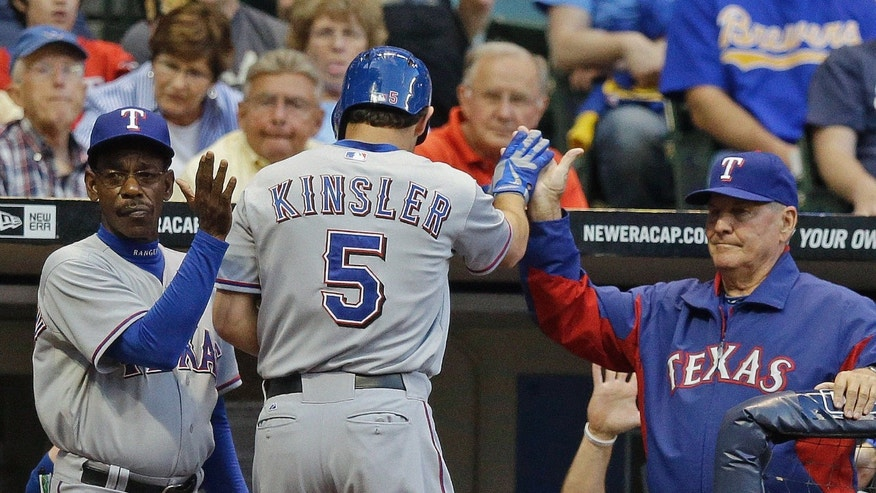 Texas Rangers' Ian Kinsler (5) is congratulated after hitting a home run during the second inning of a baseball game against the Milwaukee Brewers Wednesday, May 8, 2013, in Milwaukee. (AP Photo/Morry Gash)