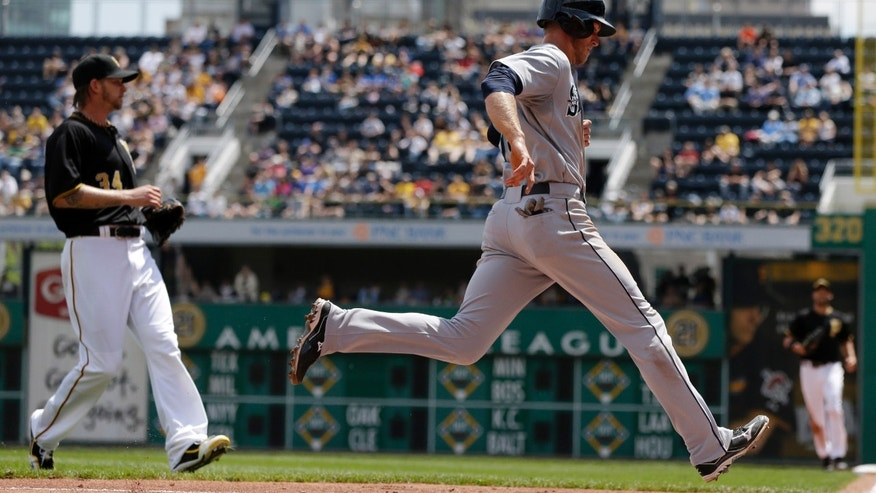 Seattle Mariners' Michael Saunders, right, scores on a passed ball as Pittsburgh Pirates starting pitcher A.J. Burnett, left, covers home during the fourth inning of an interleague baseball game in Pittsburgh, Wednesday, May 8, 2013. (AP Photo/Gene J. Puskar)